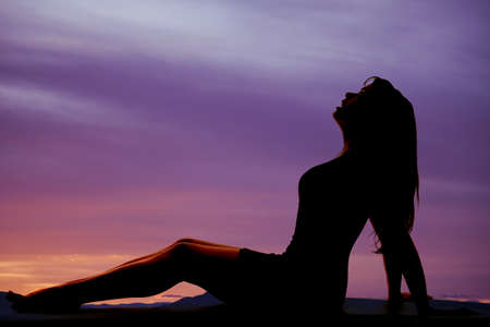 a silhouette of a woman sitting in the outdoors looking up.