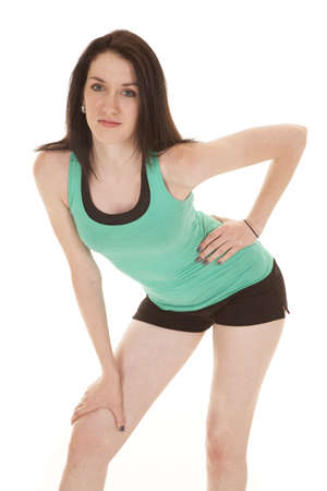 knees bent: A woman in green tank leaning over.