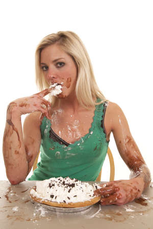 A woman is all messy and has a pie with chocolate and whipped cream. photo