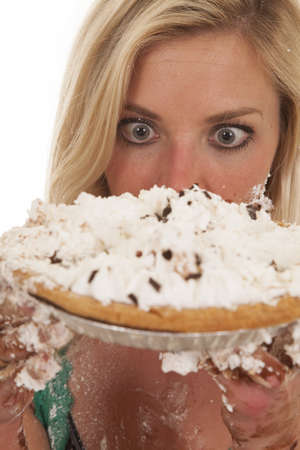 A woman has a pie by her face and is very messy.