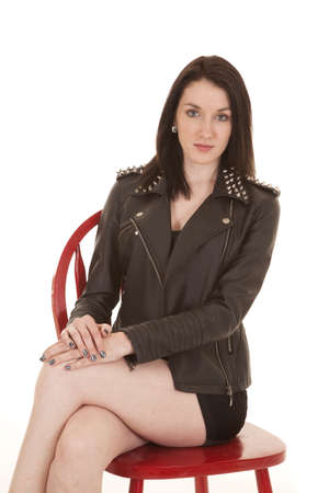 A woman sitting with legs crossed wearing a leather jacket. photo
