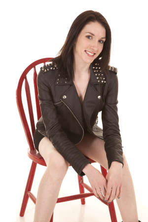 A woman in black leather jacket sitting and smiling. photo