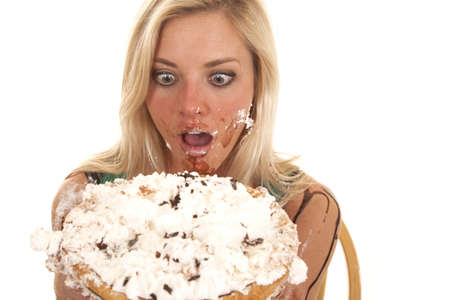 A woman is holding a pie by her face and she has it all over her. photo