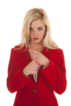 A woman in a red coat is holding a knife by her chest. photo