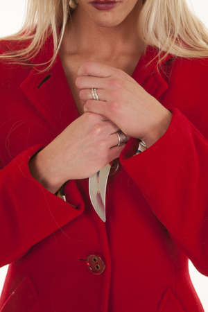A woman close up holding a knife by her chest. photo