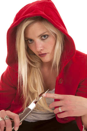 A woman wearing a red hooded jacket is holding a knife. photo