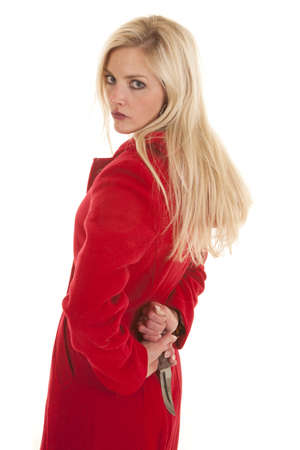 A woman wearing a red jacket is standing with a knife behind her back photo