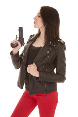 A woman in red pants and black jacket blowing gun. Stock Photo - 21354207