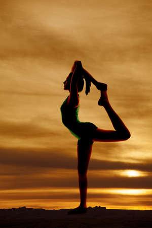 A woman doing a scorpion pose silhouette. Standard-Bild