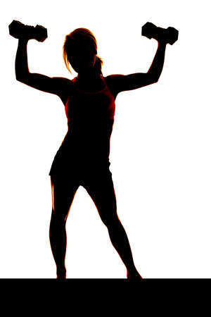 woman shadow: A woman is lifting weights up in the air silhouetted Stock Photo