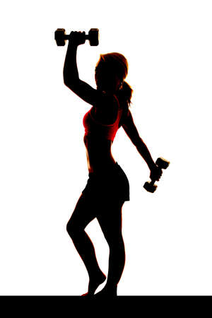 A woman is silhouetted from the side with weights. Stock Photo