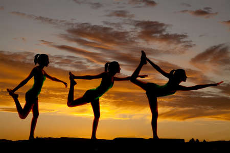 Women silhouette doing a scorpion pose in front of sky.