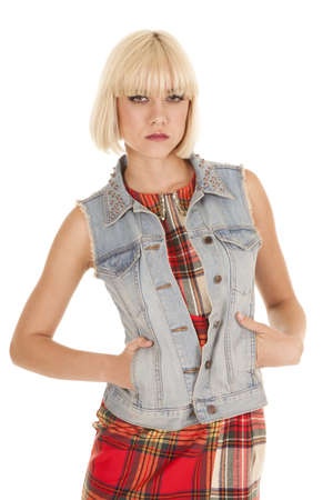 A woman in a plaid dress and a denim jacket serious expression. photo