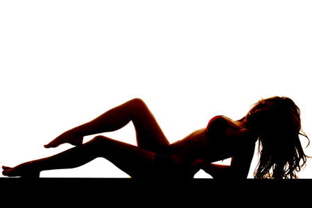 A woman is in a bikini laying back on her elbows silhouetted. photo