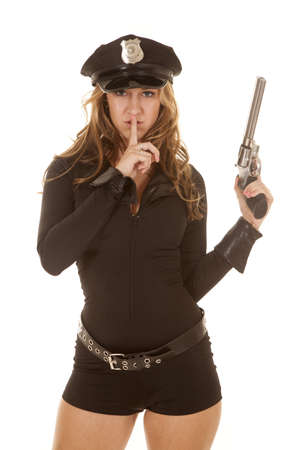 A woman cop holding up a gun with a finger to her lips. photo