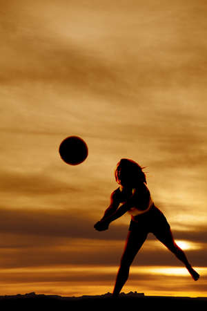 A silhouette woman playing volleyball with a beautiful sky. photo