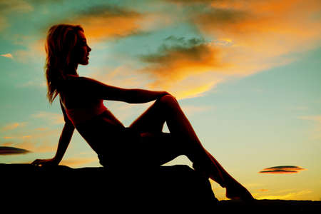 a silhouette of a woman sitting on a rock relaxing with a smile on her lips Banco de Imagens