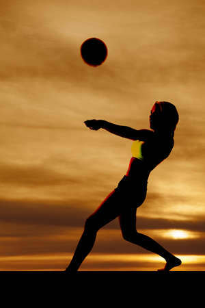 A silhouette of a woman playing volleyball with a sunset. photo