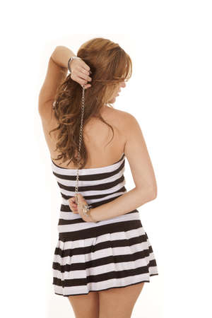 female prisoner: A woman in a jail outfit from the back with handcuffs on. Stock Photo