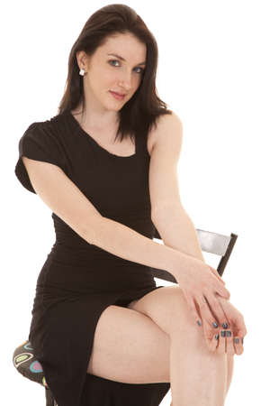 A woman sitting on a stool with a serious expression . photo
