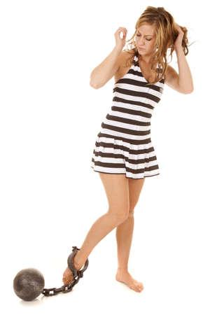 gevangen: Een vrouw in een gevangenis outfit met een bal en ketting op zijn voet. Stockfoto
