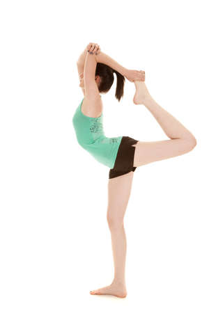 A woman doing her scorpion pose in her blue tank and shorts photo