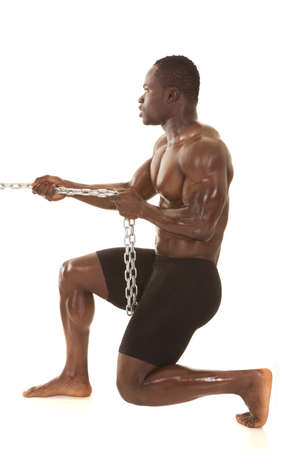 male profile: A very strong man is pulling on a metal chain.