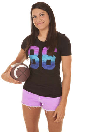 A woman in her football top holding on to a football with a smile on  her face. photo