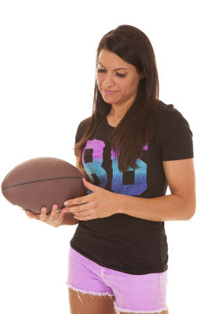 a woman looking down at her American football with a small smile on her lips. photo