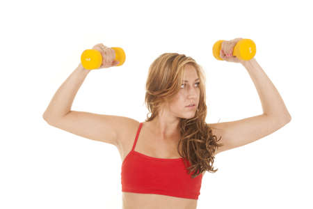 A woman in a red sports bra and yellow weights. photo