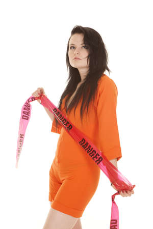 A woman in an orange prisoner jumpsuit with danger tape.