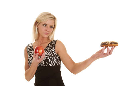 glutton: A woman looking at a doughnut and holding an apple. Stock Photo