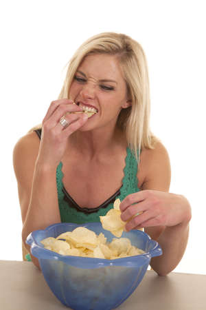 overeat: A woman eating potato chips from a blue bowl.
