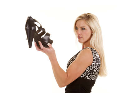 wants: A woman is holding a pair of shoes she wants. Stock Photo