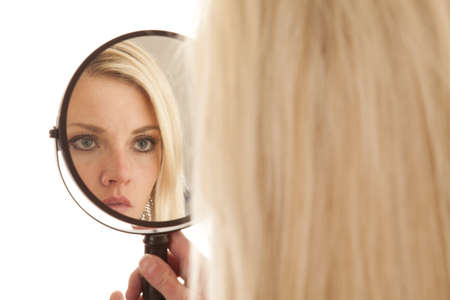 A woman is looking into a mirror up close photo