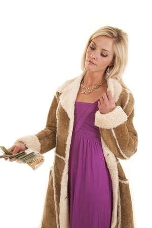 A woman in a purple dress and a coat with money. photo
