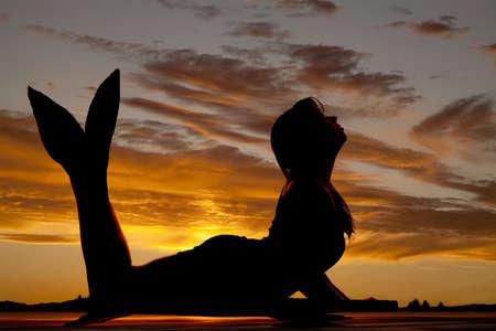 Een silhouet van een zeemeermin in de zonsondergang. Stockfoto