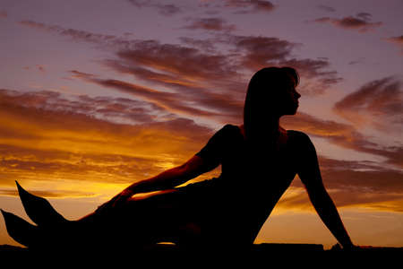 A silhouette of a mermaid in the sunset. photo