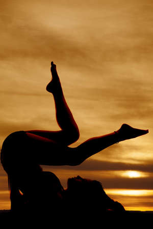 A woman laying on her back with her legs up barefoot in the sunset silhouetted.