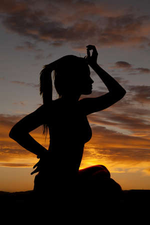 A woman in the sunset silhouetted in the sky photo