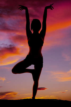 A woman doing yoga in the sunset silhouetted. photo