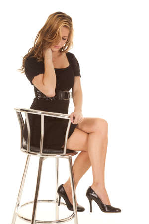 A woman in a black dress sitting on a chair with legs crossed. photo