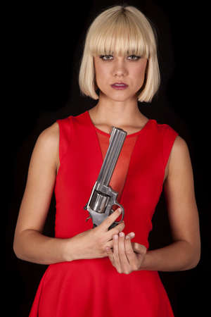 A woman in a red dress holding a revolver. photo