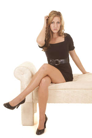 A woman is sitting on a bench in a short black dress.