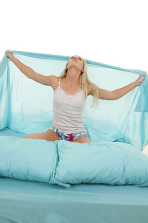 a woman holding out her sheet out while sitting in her bed. photo