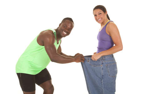A man holding on to the front of a woman's pants with a smile on their faces, because she lost weight. Stock Photo - 21553446
