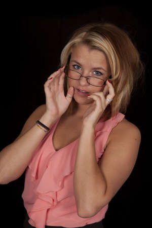 A woman holding on to her glasses in her peach tank photo