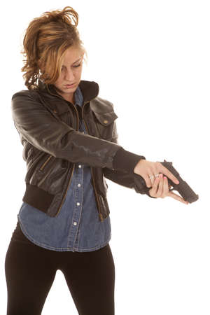 a woman in her black jacket pointing her pistol down. Stock Photo