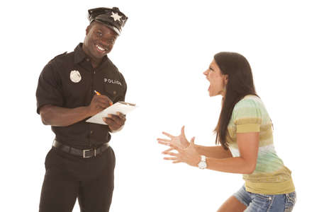A woman yelling and screaming at a policeman, and the policeman is smiling.