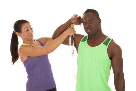A woman measuring a man's bicep with a smile on her face at how big it is. photo